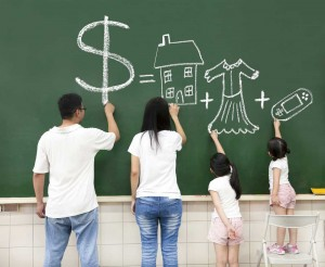family drawing their buying wish list on a blackboard