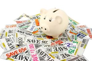 Piggy bank sitting on top of a pile of many grocery discount coupons