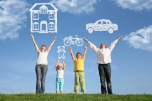 Family standing in a meadow with their hands joyfully up in the air dreaming about the things they want to buy