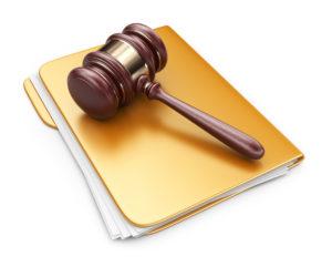 Judges gavel laying on top of a manila folder