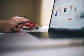 mans hand holding his credit card sitting at a table in front of his computer