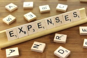 Expenses spelled out with scrabblew tokens in a scabble token holder