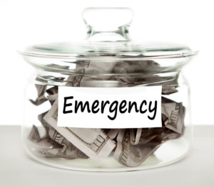 Glass jar stuffed with bank notes labeled emergency