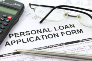calculator, glasses and pen lying on top of a personal loan application form