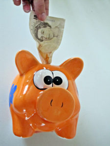rainy day money ten pound note being put into an orange ceramic piggy bank