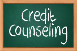 credit counseling spelled out with white chalk on a medium sized bottle green chalk board that has a wooden frame