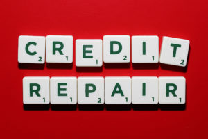 credit repair spelled out in green letters on white scrabble tokens sitting on a red background
