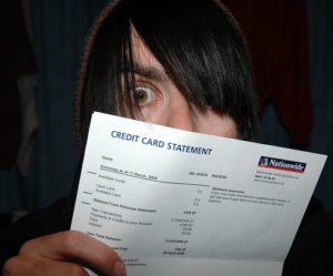 centrelink loans no credit check - man with long hair looking goggled eyed at his credit card statement